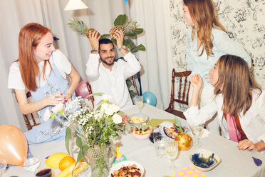 Playful man holding pineapples while sitting amidst female friends at home during dinner party - MASF09696
