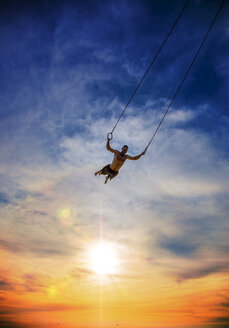 Man swinging on gymnastic rings during sunset - LUXF02072