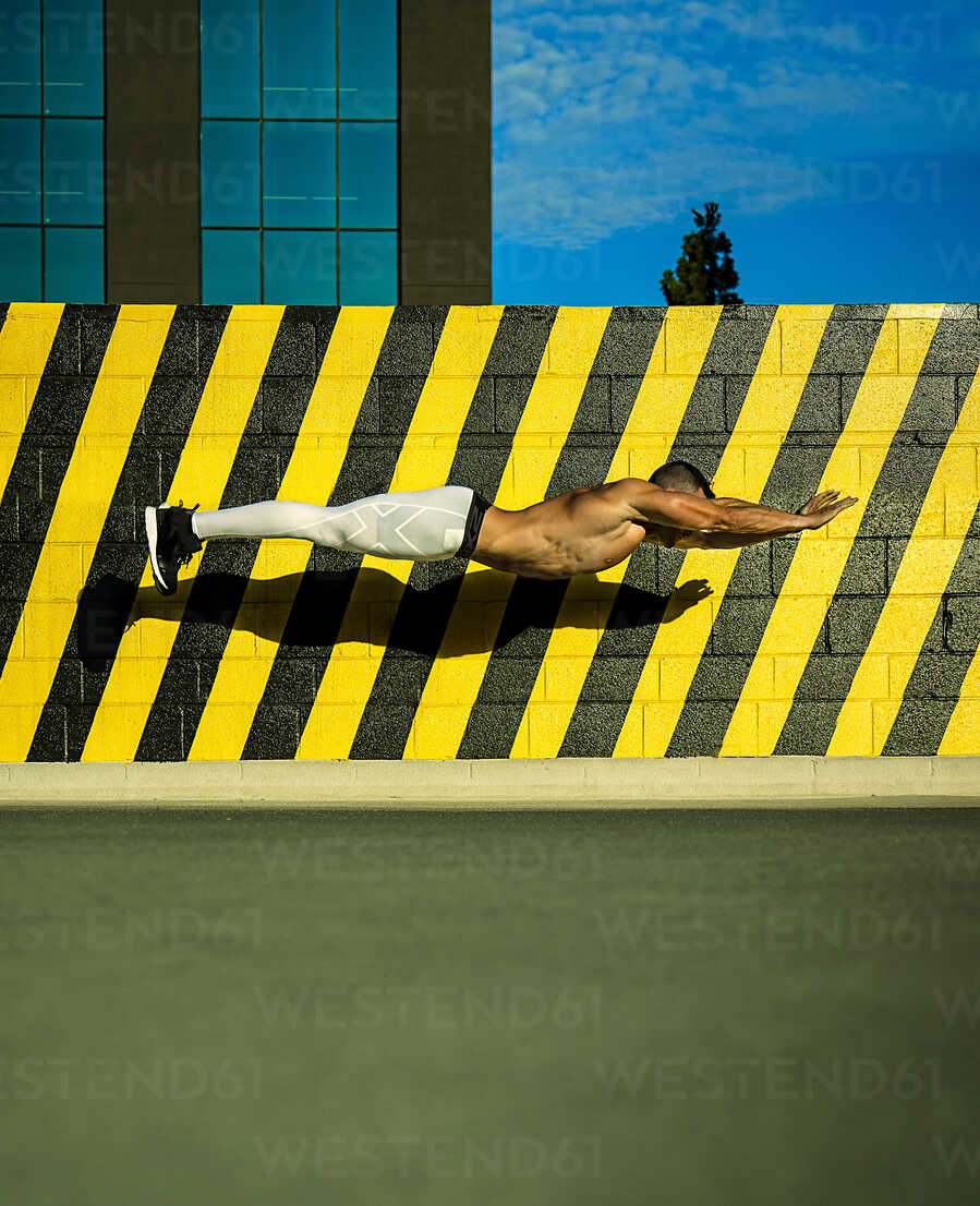 Shirtless man falling beside striped brick wall - LUXF02084 - Luxy Images/Westend61