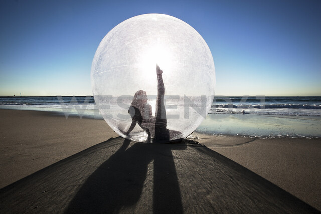 Woman doing yoga in ball on beach during sunset - LUXF02102