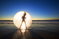 Woman dancing in ball on beach during sunset - LUXF02105