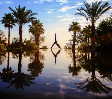 Young woman doing yoga beside swimming pool and palm trees - LUXF02120