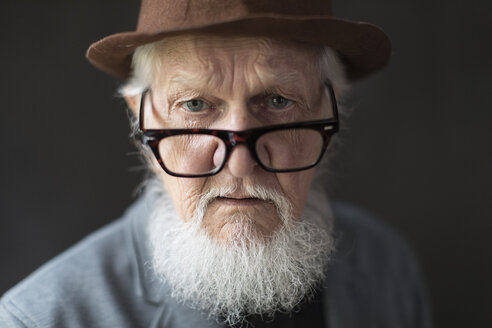 Close-up portrait of serious senior man looking over eyeglasses against black background - TGBF00329