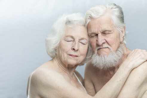 Close-up of relaxed senior couple embracing against gray background - TGBF00332