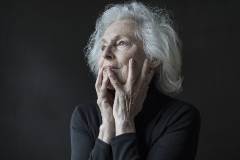 Close-up of thoughtful senior woman with hands on face against black background - TGBF00338