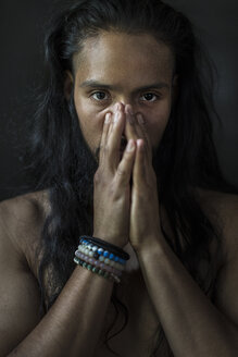 Portrait of young man with hands clasped over face against black background - TGBF00353