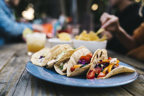 Closeup of delicious Mexican tacos in blue plate on wooden table with people in background - TGBF00419