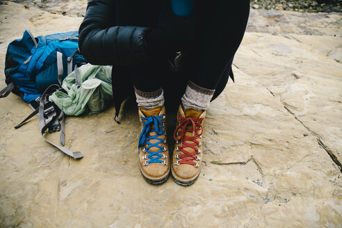 Low section of woman wearing hiking boots with red and blue shoelace sitting on rock - TGBF00431