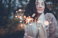 Close-up portrait of beautiful young woman holding sparklers in the forest - INGF05304