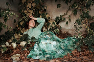 Portrait of a young woman lying down in the leaves during autumn - INGF05319