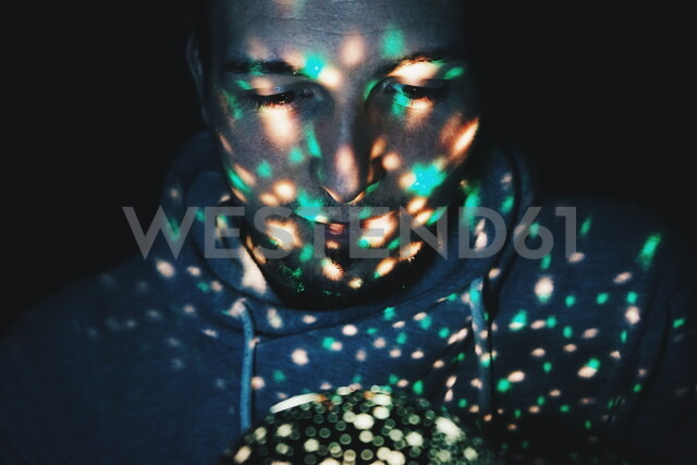 Young man illuminated by fairy lights - INGF05349