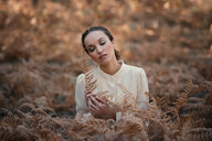 Beautiful young woman with closed eyes in autumnal landscape - INGF05379