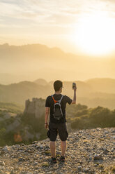 Spain, Barcelona, Natural Park of Sant Llorenc, man hiking and taking a picture of the view at sunset - AFVF01888