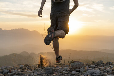 Spain, Barcelona, Natural Park of Sant Llorenc, man running in the mountains at sunset - AFVF01894
