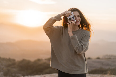 Spain, Barcelona, Natural Park of Sant Llorenc, woman taking a picture with vintage camera at sunset - AFVF01900