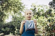 Girl posing with blackberries in plastic bag - TGBF00527