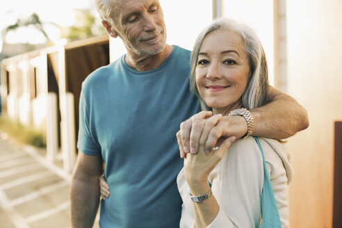 Portrait of smiling mature woman standing with man on sidewalk - TGBF00554