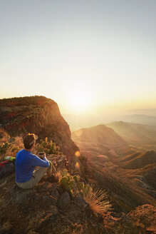 Rear view of male hiker sitting on mountain while enjoying the sunset view - TGBF00566