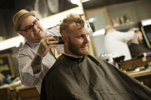 Happy male customer receiving haircut from barber at salon - TGBF00575