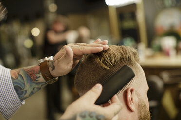 Cropped image of barber combing customer's hair at salon - TGBF00578