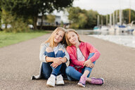 Portrait of two smiling girls sitting head to head on the ground - NMSF00277