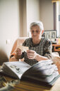 Senior woman looking at photo before adding it into a photo album - RAEF02216