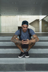 Tattooed young man sitting on stairs using smartphone - JPTF00050