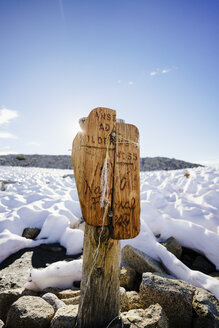 Closeup of text on wooden signboard at snow covered mountain against sky - TGBF00582