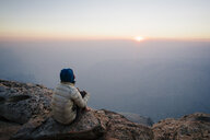 High angle view of woman sitting on cliff by mountains against sky during sunset - TGBF00585