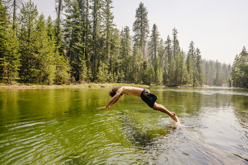 Full length of man diving in river by trees at Yosemite National Park - TGBF00588