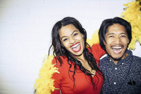 Portrait of excited Multi ethnic couple laughing at party - TGBF00606