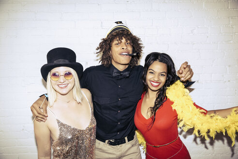 Portrait of young man standing with arms around women at party - TGBF00615