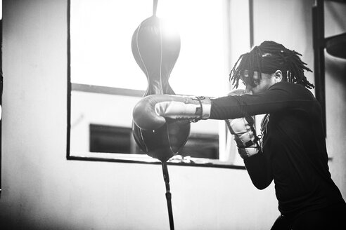 Side view of determined female boxer practicing in gym - TGBF00660