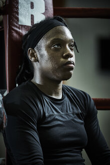 Thoughtful female boxer looking away while sitting in boxing ring at health club - TGBF00675