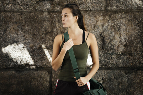 Woman In Sportswear With Shoulder Bag Standing Against Wall - TGBF00693