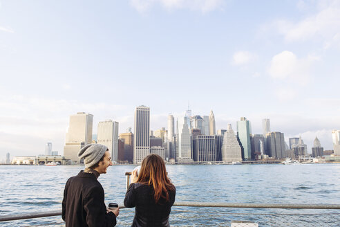 Young couple looking at Manhattan skyline from Brooklyn - TGBF00711