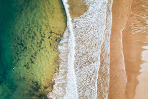 Spain, Asturias, Aerial view of surfers in the water on a beach - MGOF03823