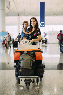 Mother holding a baby girl at the airport and pushing a trolley with the luggage - GEMF02435