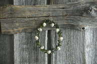 Wreath of box tree twigs with quail eggs in front of rustic wooden wall - ASF06239