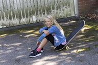 Portrait of smiling blond girl sitting on her skateboard outdoors - JFEF00907
