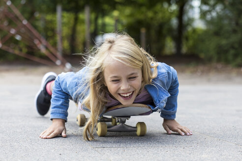 Portrait of laughing blond girl lying on her skateboard outdoors - JFEF00910