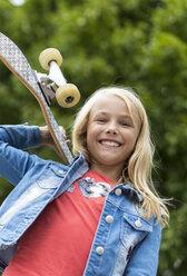 Portrait of proud blond girl with skateboard on her shoulder - JFEF00916