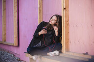 Young woman sitting outdoors listening to music - UUF15647