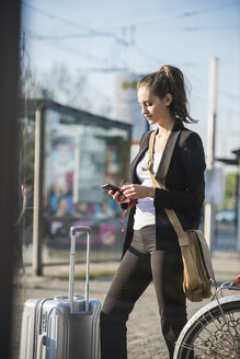 Young woman with luggage at tram station in the city checking cell phone - UUF15665