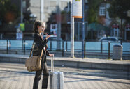 Smiling young woman with luggage at tram station in the city using cell phone - UUF15668