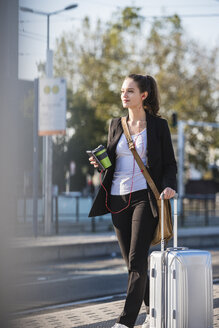 Young woman with luggage at tram station on the move - UUF15671
