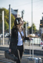 Young woman with headphones, suitcase and violin case at tram station - UUF15677