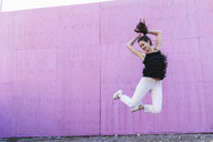 Exuberant young woman jumping in front of pink wall - UUF15689