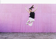 Exuberant young woman jumping in front of pink wall - UUF15692