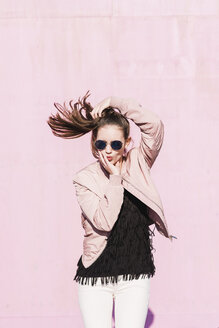 Portrait of young woman wearing sunglasses posing in front of pink wall - UUF15695